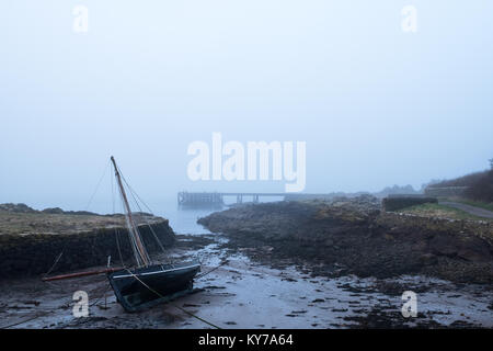 A yacht lying on its side as the tide goes out on a misty beach in Scotland. A jetty can be seen in the misty distance - Stock Photo