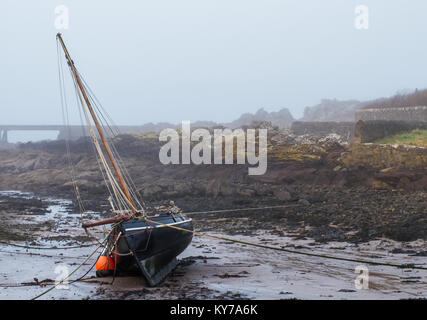 A yacht lying on its side as the tide goes out on a misty beach in Scotland. A jetty can be seen in the misty distance. - Stock Photo