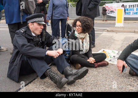 Police talk to peace campaigners blocking the road leading to the the ExCeL centre where the DSEi Arms Fair begins - Stock Photo