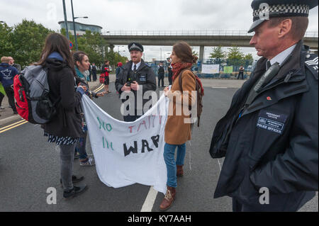 Police talk to peace campaigners holding a banner 'No Faith In War' blocking the road leading to the the ExCeL centre - Stock Photo