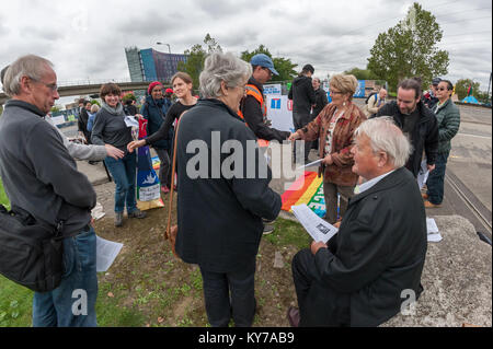 People exchange a handshake of peace at the Pax Christi led 'Prayers of Repentance' outside the ExCeL centre where - Stock Photo