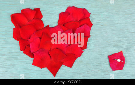 Rose petals in heart shape and one stone ring - Stock Photo