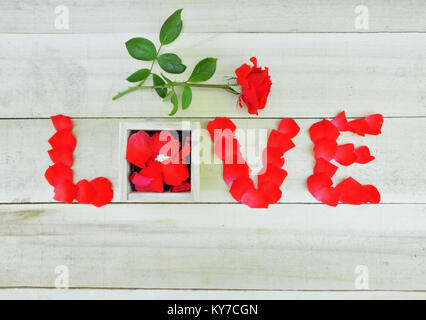 Word love written with rose petals, red rose  and box with single stone ring on wooden background - Stock Photo