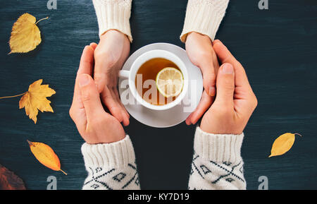 Couple Man and Woman in Love holding hands with hot tea lemon cup on dark wooden table with autumn leaves Romantic - Stock Photo