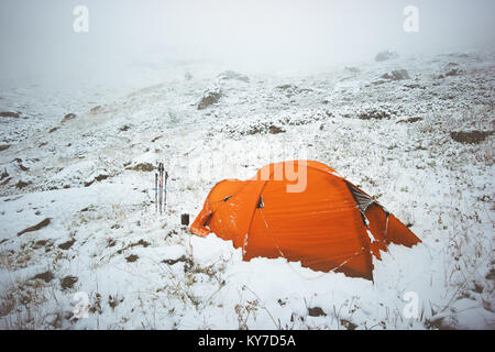Tent camping in winter mountains foggy snowy weather Travel Lifestyle concept adventure vacations outdoor - Stock Photo