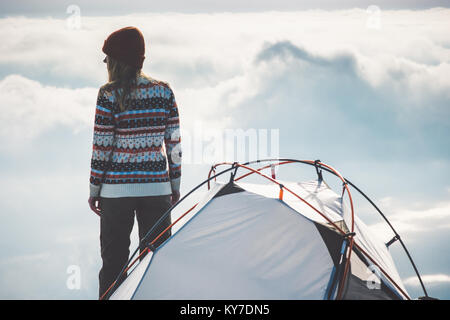 Woman Traveler on mountain summit and tent camping foggy clouds landscape on background Travel Lifestyle concept - Stock Photo