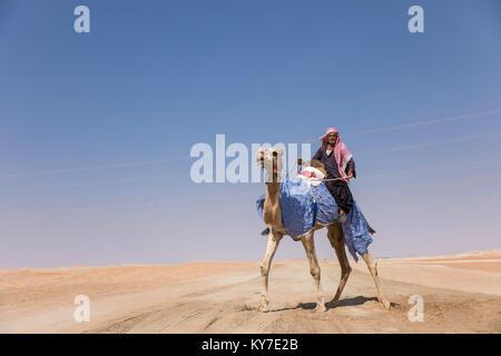 Abu Dhabi, UAE - Dec 15, 2017: Old man riding his camel in the desert during Al Dhafra camel festival. - Stock Photo