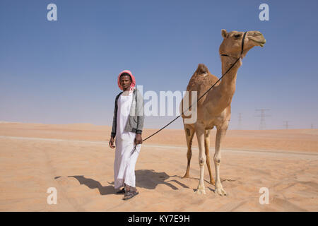 Abu Dhabi, UAE - Dec 15, 2017: A proud man posing with his show camel during Al Dhafra camel festival. - Stock Photo