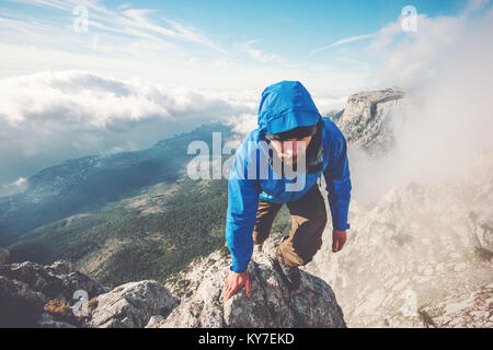 Man Traveler climbing on mountain summit over clouds Travel Lifestyle success concept adventure active vacations - Stock Photo