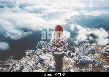 Woman traveler on mountain summit over clouds enjoying aerial view Travel Lifestyle success concept adventure active - Stock Photo