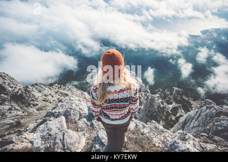 Woman traveler on mountain summit over clouds Travel Lifestyle success concept adventure active vacations outdoor - Stock Photo