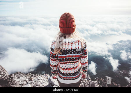Woman traveler standing on mountain summit over clouds enjoying aerial view Travel Lifestyle success concept adventure - Stock Photo