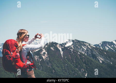 Happy Woman showing heart love by hands hiking in mountains with backpack Travel Lifestyle success concept adventure - Stock Photo