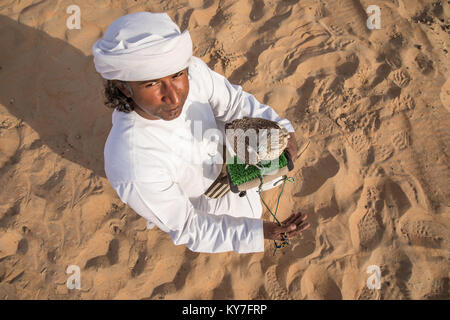Abu Dhabi, UAE - Dec 15, 2017: Man in a traditional emirati dress proudly posing with his trained show falcon. - Stock Photo