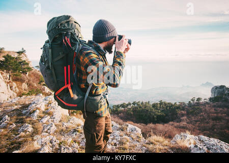 Man traveler photographer with backpack and camera taking photo of mountains Travel Lifestyle hobby concept adventure - Stock Photo
