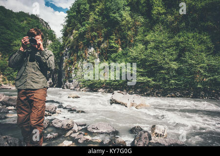 Man traveler photographer with camera taking photo of mountains Travel Lifestyle hobby concept adventure summer - Stock Photo