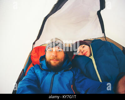 Couple travelers family Man and Woman taking selfie inside tent camping girl in sleeping bag tourism hiking equipment - Stock Photo