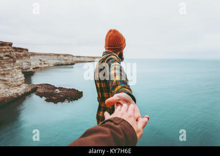 Couple Man and Woman holding hands follow enjoying cold sea landscape on background Love and Travel emotions Lifestyle - Stock Photo