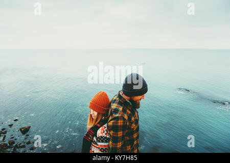 Couple in love Man and Woman back to back standing above sea Traveling together happy emotions Lifestyle concept. - Stock Photo