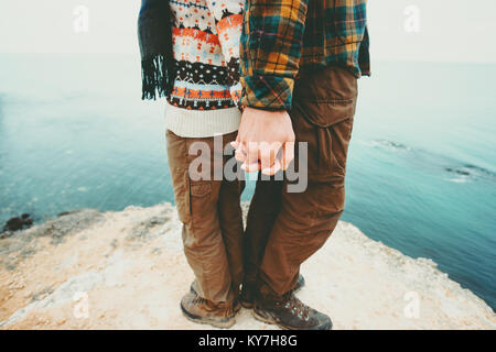 Couple Man and Woman holding hands standing on cliff above sea landscape Love and Travel happy emotions Lifestyle - Stock Photo