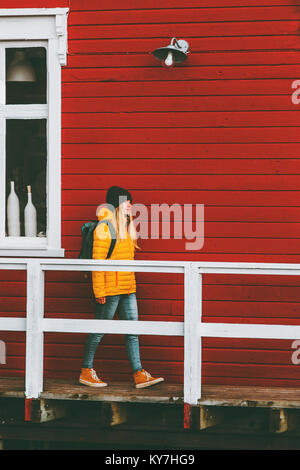 Traveler woman walking in Norway village red house wall on background Travel Lifestyle concept winter vacations - Stock Photo