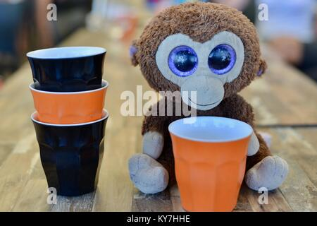 Big eyed toy monkey sitting on a cafe table among an arrangement of   of black and orange plastic cups, Sunshine - Stock Photo