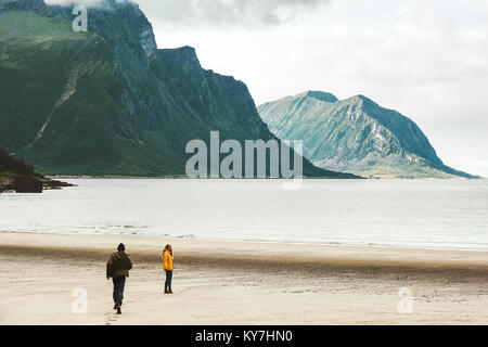 Couple in love Man running to Woman at sea Norway beach Travel happy emotions Lifestyle concept romantic vacations - Stock Photo