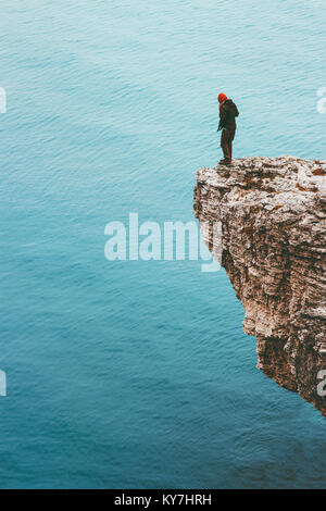 Traveler standing on cliff edge above sea alone Travel Lifestyle concept adventure active vacations outdoor solitude - Stock Photo