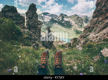 Feet trekking boots and mountains landscape on background Travel Lifestyle adventure vacations concept - Stock Photo