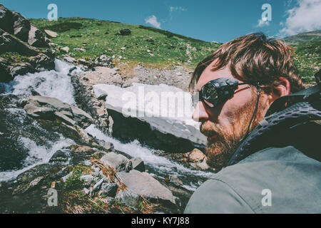 Bearded Man wearing mountain sunglasses hiking Travel Lifestyle concept adventure  vacations survival outdoor - Stock Photo