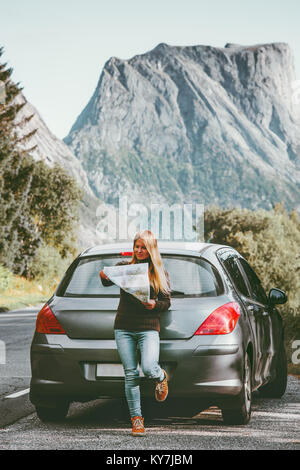 Young Woman traveling by rental car roadtrip with map in Norway Travel Lifestyle concept adventure weekend vacations - Stock Photo