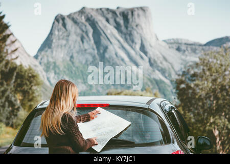 Woman traveling by car on road trip with map planning route Lifestyle concept adventure vacations outdoor - Stock Photo