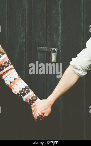 Love Couple hands holding forever together Lifestyle wooden background and lock over people taboo concept - Stock Photo