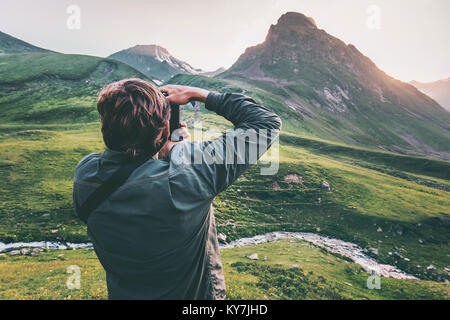 Man blogger photographer taking photo of sunset mountains Travel Lifestyle hobby concept adventure active vacations - Stock Photo