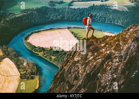 Hiking adventure in Norway mountains Man with backpack on cliff Travel lifestyle concept active weekend summer vacations - Stock Photo