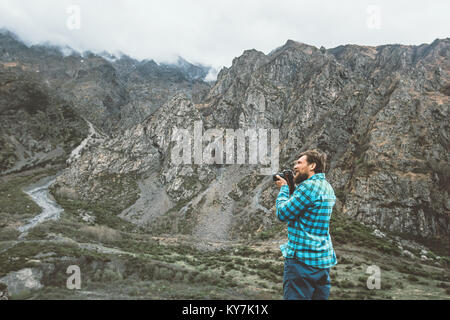 Man photographer with camera taking photo of foggy mountains Travel Lifestyle hobby concept adventure active vacations - Stock Photo