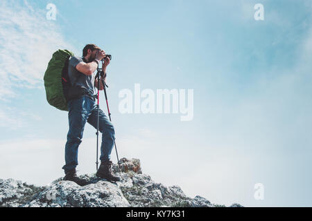 Man photographer with big backpack and camera taking photo of mountains Travel Lifestyle hobby concept adventure - Stock Photo