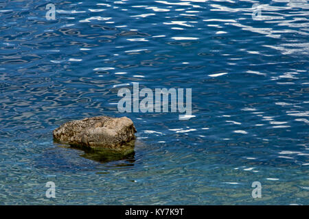 Rock in calm blue rippling water on the coast of the Adriatic sea - Stock Photo