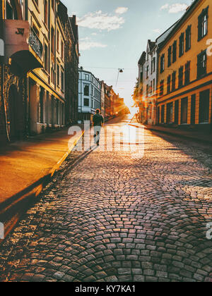 Man tourist walking in sunset street Travel Lifestyle concept vacations cobblestone road Alesund city in Norway - Stock Photo