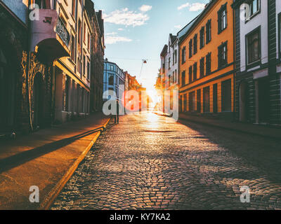 Man walking alone at sunset street Travel Lifestyle concept vacations cobblestone road city in Norway - Stock Photo