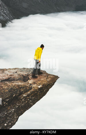 Man traveler standing on Trolltunga rocky cliff edge in Norway mountains Travel Lifestyle adventure concept extreme - Stock Photo