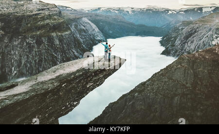 Couple Man and Woman on Trolltunga cliff raised hands mountains Love and Travel emotions Lifestyle concept. Young - Stock Photo