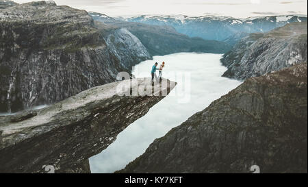 Couple Man and Woman on Trolltunga cliff mountains Love and Travel emotions Lifestyle concept. Young family traveling - Stock Photo