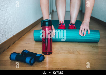 Woman preparing for workout at home with dumbbells, yoga mat and bottle of water. Healthy habit of drinking more - Stock Photo