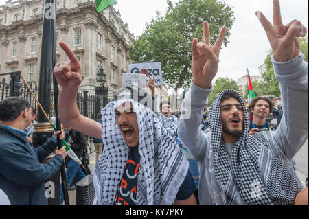 Young pro-Palestine demonstrrators outside Downing St gesture at pro-Israel protesters behind me outside Downing - Stock Photo