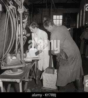 1950s, historical, a female dairy worker in a white-coat putting finished from the butter churn butter onto weighing - Stock Photo