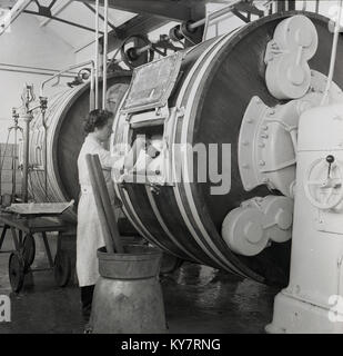 1950s, historical, female dairy worker in white coat checking the butter that has been made inside a large barrel - Stock Photo