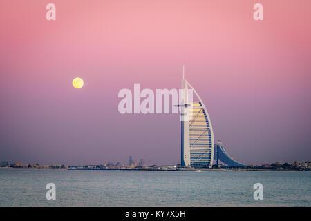 Dubai, UAE, December 13, 2016: full moon is rising over Burj Al Arab - the world's only 7-star luxury hotel - Stock Photo
