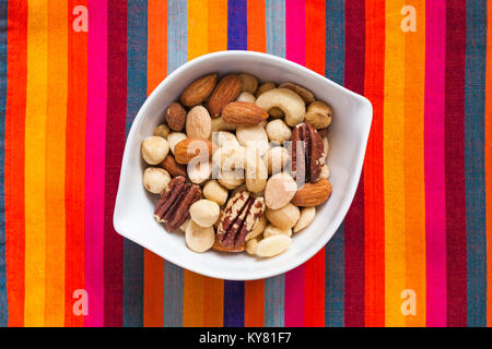 White bowl of Tesco finest roasted nut selection on colorful striped background. Mixed roasted nuts delicately seasoned - Stock Photo