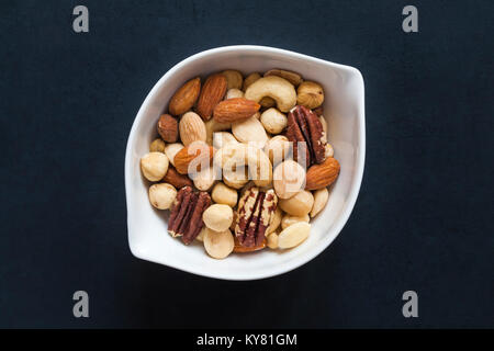 White bowl of Tesco finest roasted nut selection isolated on black background. Mixed roasted nuts delicately seasoned - Stock Photo